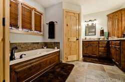 main level master private bath with Jacuzzi tub, separate shower, and dual sinks image 1
